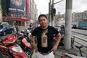 A man wearing a T-Short with an image of a vokda bottle in Shanghai.