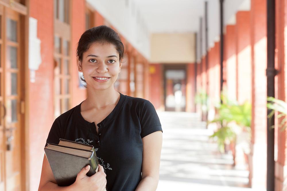 A young female Indian university student holding her book in cloistered walkway with sunbeams shining through