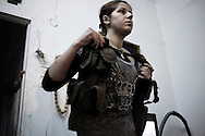"SYRIA, ALEPPO : A Kurdish woman fighter of the ""Popular Protection Units"" (YPG) stands between two comrade fighters inside a building in the majority-Kurdish Sheikh Maqsud district of the northern Syrian city of Aleppo, on April 16, 2013. ALESSIO ROMENZI"