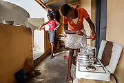 "Navrongo, Ghana.  Lamisi Didera, age 20, and her sister Jessica, age 15, prepare dinner on their LPG stove. Lamisi purchased the LPG stove for her mother because her mother told her she was not feeling well and complained when she was cooking. Lamisi thought the smoke was bothering her, so she bought her the stove about three years ago. Lamisi added,  ""Cooking on the LPG stove will also save her time, and the LPG does not need constant monitoring. It is also easier to time the food because you can turn the heat up or down on the LPG gas which is not as consistent when using three stones."" Jessica loves to use the LPG and thinks the wood and coal is too much trouble. Magdalene said that her mother is getting used to using the LPG stove after years of cooking on three stones or charcoal in a coal pot."