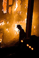 JEROME A. POLLOS/Press ..A firefighter surveys the flames during a house fire Wednesday at Mica Bay on Lake Coeur d'Alene.