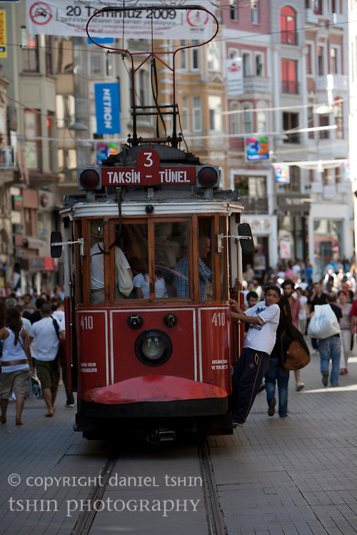 Local boys hanging off the historic tram full of passengers as it travels along ?stiklal Avenue in Beyo?lu, a walking street which is full of pedestrians.