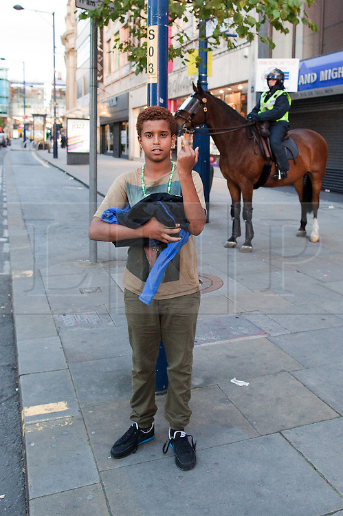 © Licensed to London News Pictures. 09/08/2011. Manchester, UK. Destruction and looting  across the city centre by gangs. Shops are smashed, looted. This boy brazenly flaunts stolen trainers in front of watching police. Photo credit : Joel Goodman/LNP