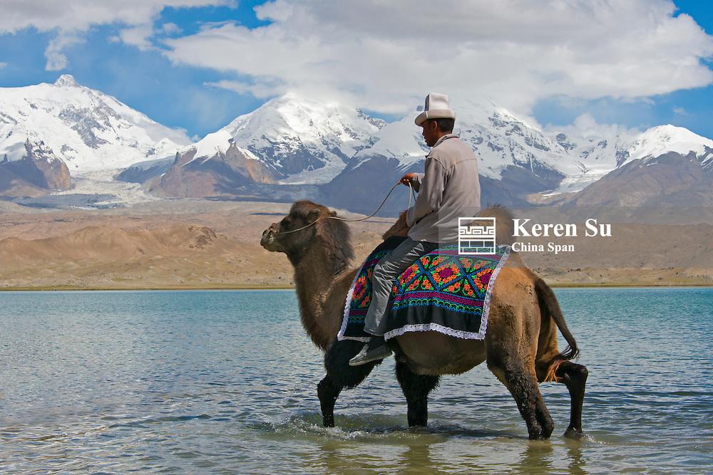 Kirghiz man riding on camel by Karakuli Lake, Xinjiang Province, Silk Road, China