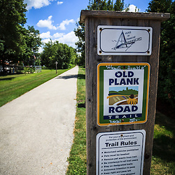 Photo of Old Plank Road Trail Sign wooden post in Frankfort Illinois. The Old Plank Road Trail is a public recreational walking and biking path and was originally used for railroad train tracks.