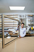 Portrait of a happy young man working on big picture frame in workshop