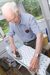 Elderly Carer who looks after wife; who has Alzheimer's disease; at home doing the ironing,