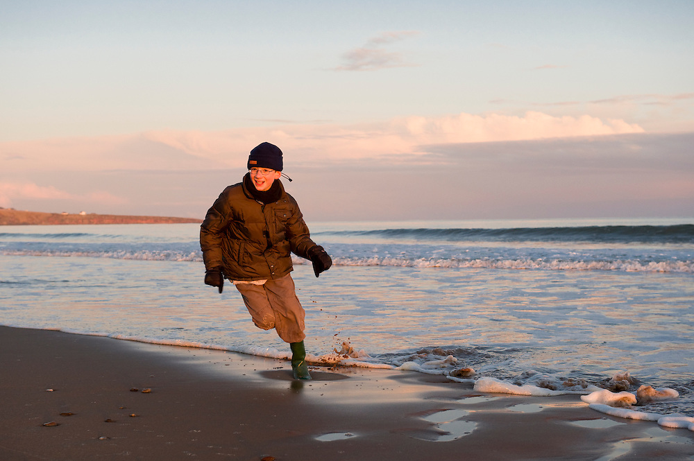 Boy playing at the ocean's edge in winter, Scotland