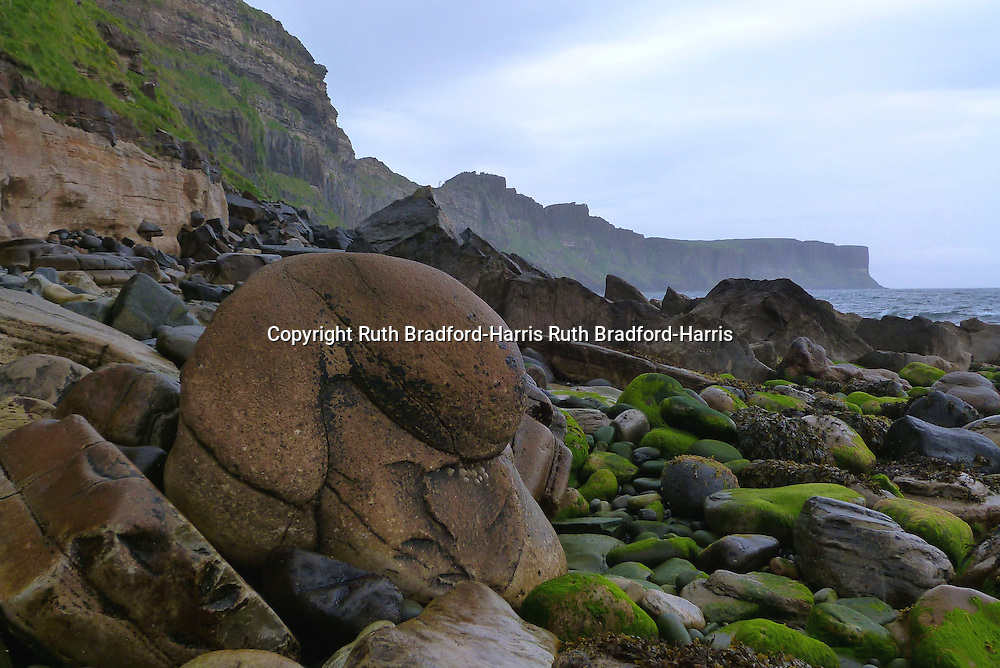 A huge, rounded, water-worn concretion, fallen from the cliffs onto the beach at Valtos, Trotternish, Isle of Skye. The stunning columnar basalt cliffs of Kilt Rock are visible in the distance.  <br />