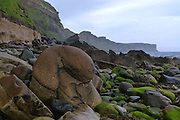 A huge, rounded, water-worn concretion, fallen from the cliffs onto the beach at Valtos, Trotternish, Isle of Skye. The stunning columnar basalt cliffs of Kilt Rock are visible in the distance.  <br /> <br /> The Valtos Sandstone Formation, named after this type locality, displays spectacular cannonball-like Calcite concretions embedded in the strata of the sea cliffs.<br /> <br /> Date taken: 15 June 2016.