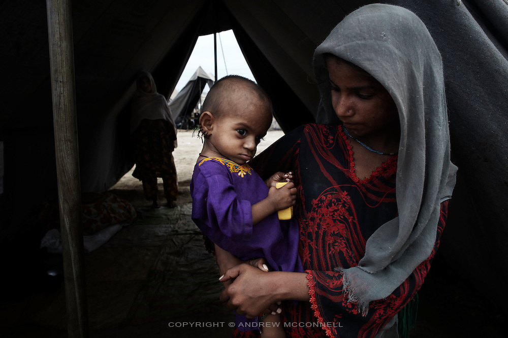10 Year old Mia Gulla holds her 1 year old sister Faminda in a camp for people displaced by the floods, in Sukkur, Sindh Province, Pakistan.