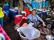 20 JUNE 2018 - BANGKOK, THAILAND: A fish monger uses a plastic bag on the end of a stick to keep flies off her fish at Makkasan Market, a small local market in central Bangkok. Officials in Thailand are wrestling with Thais use of plastic bags. The issue became a public one in early June when a whale in Thai waters died after ingesting 18 pounds of plastic. In a recent report, Ocean Conservancy claimed that Thailand, China, Indonesia, the Philippines, and Vietnam were responsible for as much as 60 percent of the plastic waste in the world's oceans.      PHOTO BY JACK KURTZ