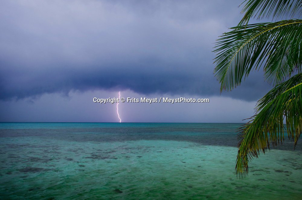 Glovers Reef Atoll, Dangriga, Belize, April 2012. A thunderstorm unleashes a waterspout, lots of lightning and even more rain onto the camp. Thirty six miles offshore of the Belize mainland lie a group of tropical islands cradled within a turquoise lagoon and surrounded by a living coral reef. Glover's Reef Atoll is considered one of the richest tropical marine environments in the entire Caribbean Sea. The private island camp is perched on the southern edge of the atoll and the base for sea kayaking and kayak sailing, snorkeling, diving, and fishing. Photo by Frits Meyst/Adventure4ever.com