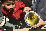 Residents of Jaibheem Nagar, pop. 10000, a large slum located near the banks of the Kali river (East), Meerut District, Uttar Pradesh, India, are showing the contaminated yellow-coloured water from one of the hand-pumps many residents use as the only source for drinking and washing, on Sunday, Mar. 16, 2008.