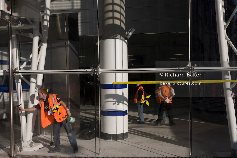 Emplyee wipes glass of the newly-finished Blackfriars mainline Station in the City of London. A larger and more accessible Blackfriars Underground station reopened for public service to accommodate more than 40,000 passengers every day.