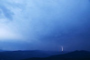 A lightning bolt strikes over the Purcell Mountains during a thunderstorm in summer. Kootenai National Forest, northwest Montana.