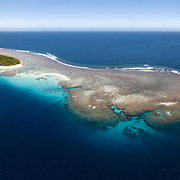 Aerial panorama of Fonua'one'one Island in the Vava'u island group of the Kingdom of Tonga, with a boat in the foreground for scale. From this perspective, it is clear that the island comprises only a small part of the entire reef and sand structure, with most of Fonua'one'one being coral reef that submerges at higher tides. This image was created during an extreme low tide just after the full moon. Fangasito Island is visible in the background.