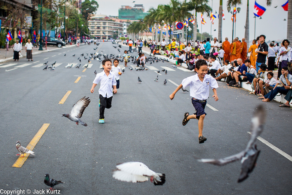 02 FEBRUARY 2013 - PHNOM PENH, CAMBODIA: Boys chase pigeons down an empty Sisowath Quay, Phnom Penh's riverfront boulevard that is normally choked with cars and motorcycles. Much of Phnom Penh has been shut down to honor former King Norodom Sihanouk, who ruled Cambodia from independence in 1953 until he was overthrown by a military coup in 1970. Only bars, restaurants and hotels that cater to foreign tourists are supposed to be open. The only music being played publicly is classical Khmer music. Sihanouk died in Beijing, China, in October 2012 and will be cremated during a state funeral royal ceremony on Monday, Feb. 4.     PHOTO BY JACK KURTZ