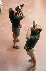 Tourists at the Dali Museum; Figueres; with one man using camera; and another using video camera,