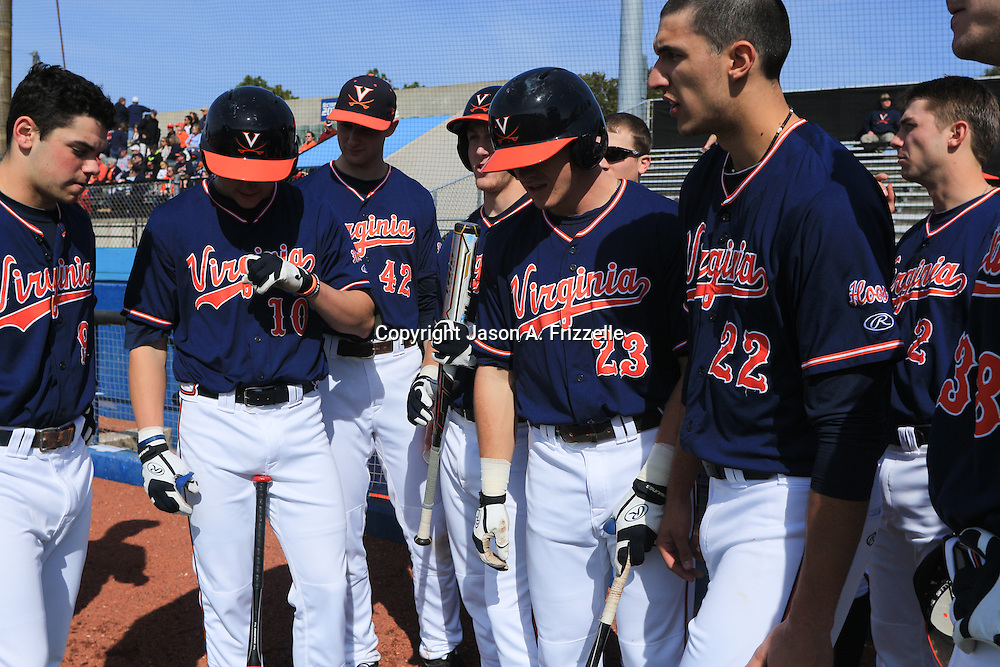 Members of The University of Virginia gather in their dugout before the start of their season opener against The University of Kentucky. The university of Kentucky faced the University of Virginia in the opening game of the Hughes Brothers Challenge Friday February 14, 2014 at Brooks Field on the campus of the University of North Carolina at Wilmington in Wilmington, N.C. (Jason A. Frizzelle)