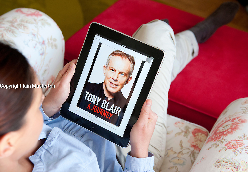 Woman using iPad tablet computer to read autobiography of Tony Blair The Journey on ebook