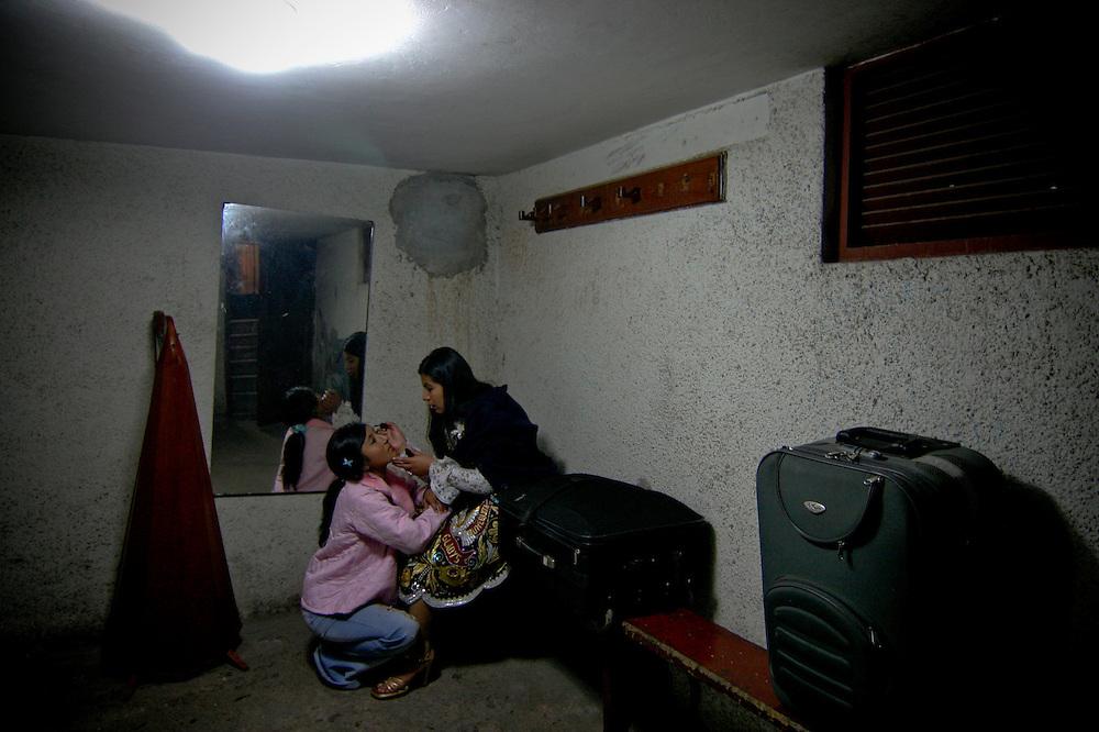 Yanet Acuña se maquilla con la ayuda de una amiga que es tambien cantante de huayno , en el interiordel camarin.