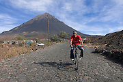 Cyclist with vulcano in background. Fogo. Cabo Verde. Africa.
