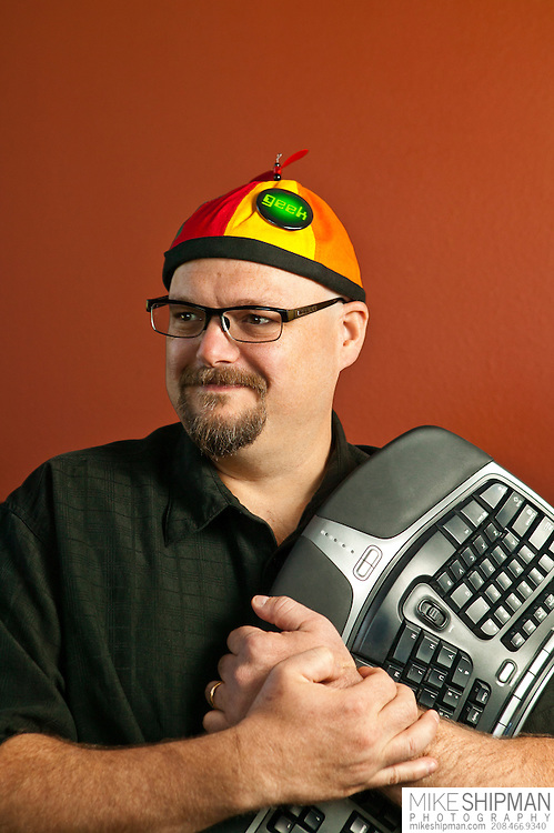"Portrait of a man wearing a colorful beanie and ""Geek"" pin, hugging a computer keyboard. MR."