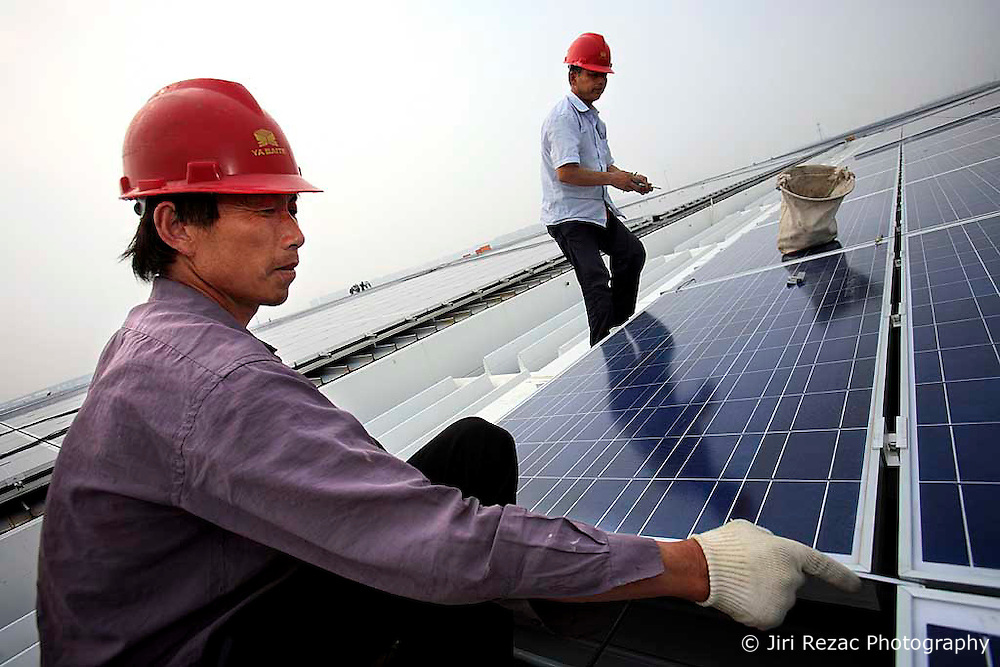 CHINA SHANGHAI HONGQIAO 19MAY10 - Workers install solar photovoltaic panels on the roofs of the Hongqiao Passenger Rail Terminal in Shanghai, China. There are a total of 23000 solar panels planned for the CECIC-funded project, each panel with a production capacity of 280 KWh to feed into the electricity grid...jre/Photo by Jiri Rezac / The Climate Group..© Jiri Rezac 2010