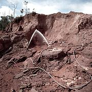 Brasile, Amazzonia, garimpo de Juma. Le miniere a cielo aperto del garimpo de Juma, dove la vita dei minatori scorre tra pericolo per un lavoro al limite e deforestazione incontrollata. Aspettando di trovare l'oro che cambi la loro vita. In questa foto due minatori distruggono con forti getti d'acqua una piccola montagna, per poi analizzare il fango creato. Brazil, Amazonia, garimpo de Juma. The open pit mines of garimpo de Juma, where the miners work flows between danger and uncontrolled deforestation. Waiting to find the gold that changes their lives. In this photo two miners with strong water jets destroy a small mountain, and then analyzing the mud created.