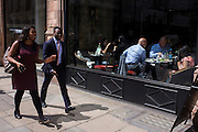Londoners walk past a classy cafe on Piccadilly in central London.