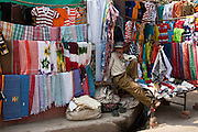 Stallholder selling clothes and sari fabrics and other textiles at Varanasi, Northern India