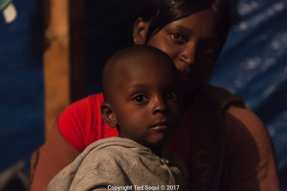 A mother with her son.<br /> Haitian immigrants inside a shelter for deportees located near the Zona Rosa. Many of the Haitian refugees sleep on wooden pallets covered with donated blankets, and wear donated clothing.<br /> Haitian immigrants.<br /> Tijuana, Mexico.