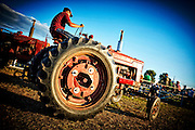 Farmer driving antique tractor at summer county fair tractor show