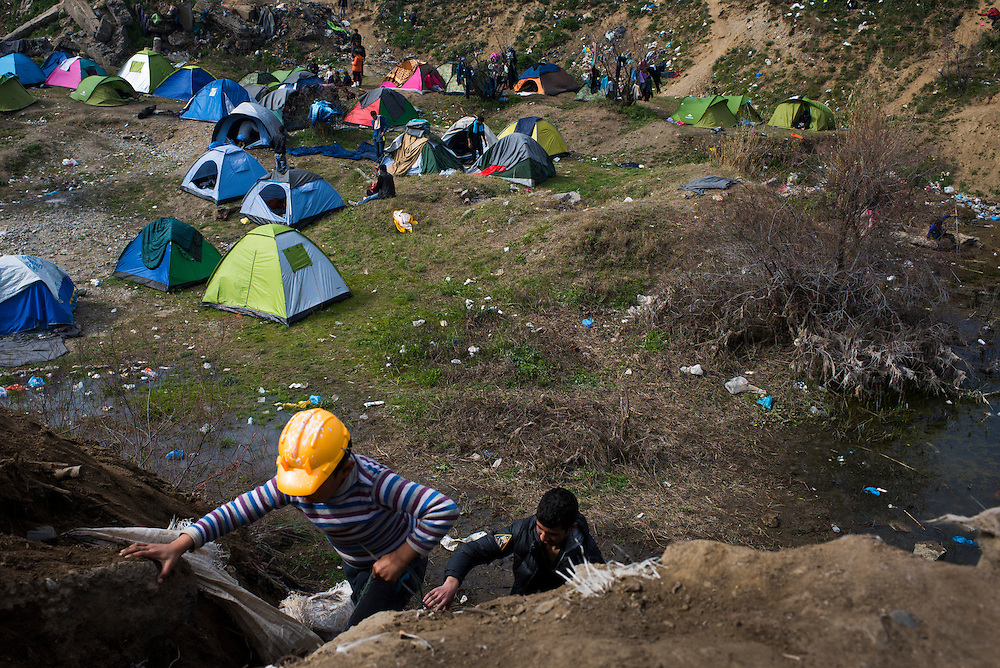Migrants climb an embankment at a refugee camp on the Macedonian (FYROM) border on March 6, 2016 in Idomeni, Greece.