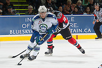 KELOWNA, CANADA - OCTOBER 7: Jay Merkley #12 of Swift Current Broncos skates with the puck with Nick Merkley #10 of Kelowna Rockets in pursuit during the first period on October 7, 2014 at Prospera Place in Kelowna, British Columbia, Canada.  (Photo by Marissa Baecker/Getty Images)  *** Local Caption *** Jay Merkley; Nick Merkley;