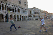 Photographers bend their knees  outside the Doge's Palace in Piazza San Marco, Venice, Italy.