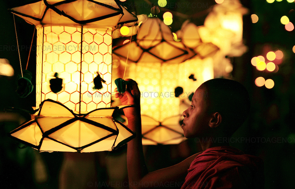 A young monk adjusts a lantern , Colombo Sri Lanka..Vesak is the most significant period in the Buddhist calendar. It celebrates the birth, enlightenment, and death of the Buddha..