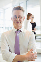 Portrait of confident businessman standing arms crossed in office