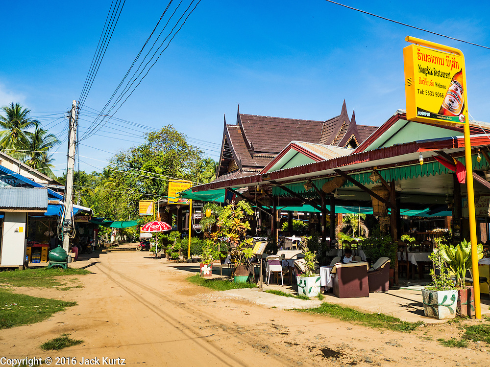 19 JUNE 2016 - DON KHONE, CHAMPASAK, LAOS: The main street in Don Khone village on Don Khone Island. Don Khone Island, one of the larger islands in the 4,000 Islands chain on the Mekong River in southern Laos. The island has become a backpacker hot spot, there are lots of guest houses and small restaurants on the north end of the island.    PHOTO BY JACK KURTZ