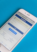 Gold and white Apple iPhone 6 with a Facebook log in screen against a blue background