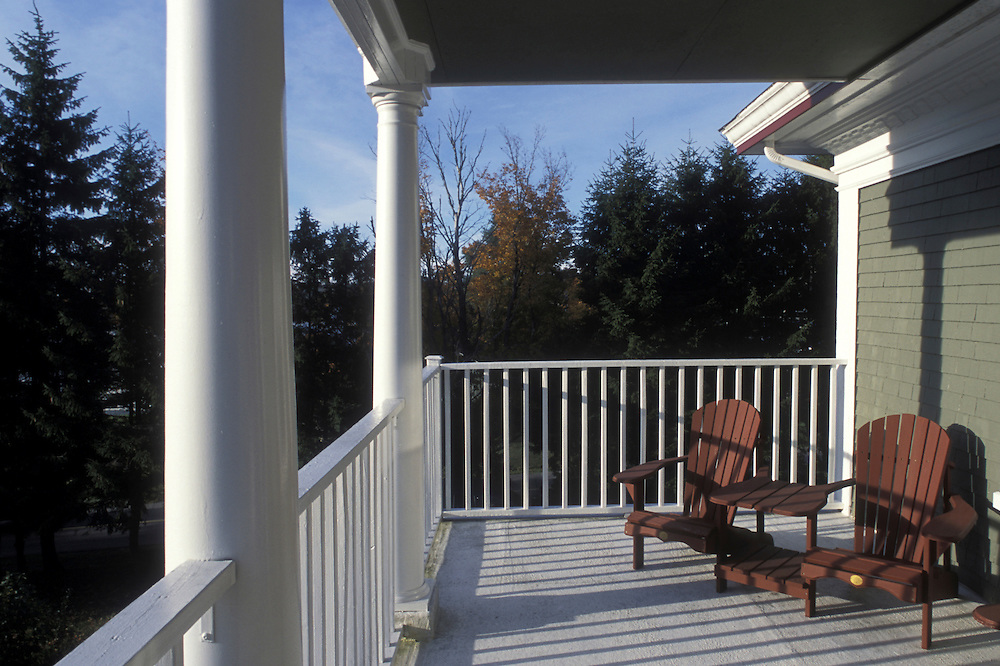 Canada, Nova Scotia, Lunenburg, Wooden chairs line balcony at Arbor View Inn on autumn morning