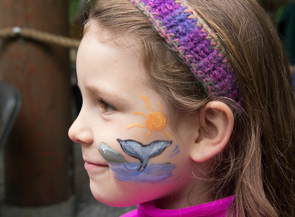 A young girl is proud of her whale and sun face paint. MR