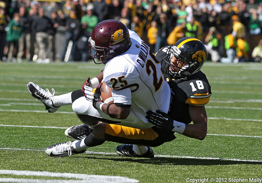 September 22 2012: Central Michigan Chippewas wide receiver Courtney Williams (25) is pulled down by Iowa Hawkeyes cornerback Micah Hyde (18) after a catch during the second half of the NCAA football game between the Central Michigan Chippewas and the Iowa Hawkeyes at Kinnick Stadium in Iowa City, Iowa on Saturday September 22, 2012. Central Michigan defeated Iowa 32-31.