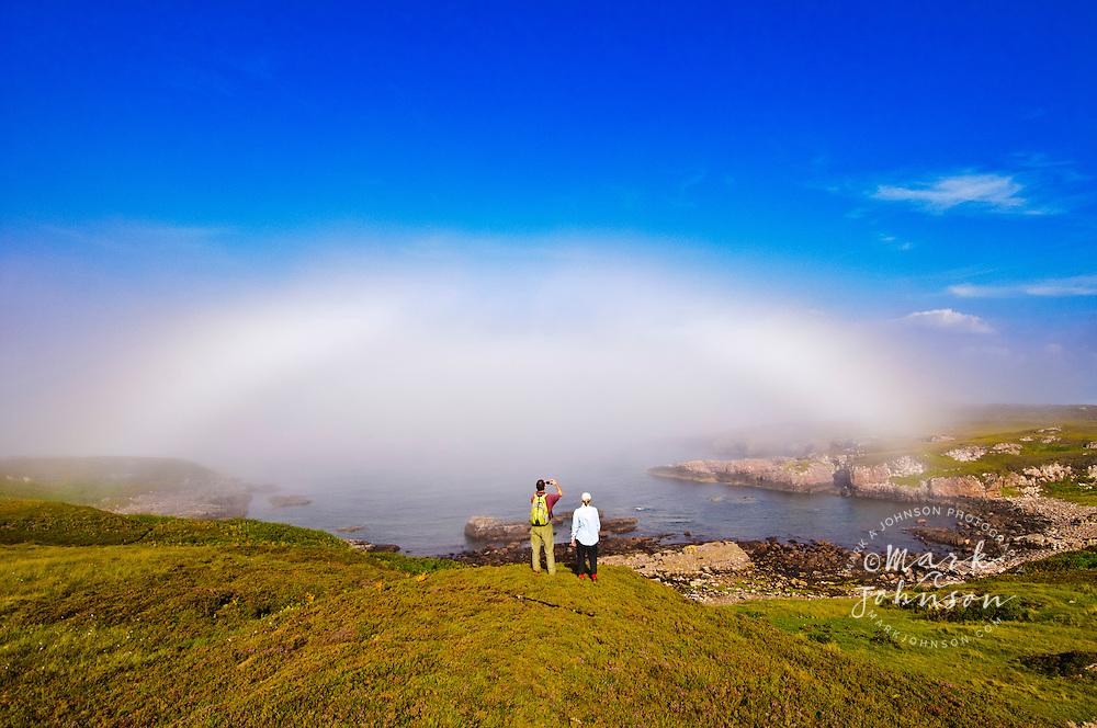 "Couple taking a photo of a ""Fogbow"", interesting weather phenomenon, Cove, Scotland, UK"