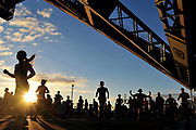 Competitors pass beneath the Harbour Bridge as they take part in the half marathon running race in Sydney, Australia.
