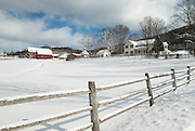 Near Cooperstown, Otsego County, NY.<br />     The farm had a meadow for a front yard, with a stream running through it and bordered by a post and rail fence, topped with a frosting of snow.  The barriers may be there to contain grazing horses in summer, or maybe it's just to keep me out.  Rightfully so, because it looks like a perfect place to walk into the middle of and plop down to soak it all in.  But the borders can't keep out the elements.   Snow falls where it will, a trespassing wind was beginning to blow a trail of fine snow crystals off the barn roofs, and clouds moved at a good clip across the ridge.  This was a frigid day in upstate NY, and I was cursing at how fast the heat was going out of my fingers, rushing to get back inside my car idling on the edge of the ditch behind me.   But the perfect, untouched field of snow punctuated by the red barns commanded me to stop, and I took the scene in from the fenceline, happy to observe from outside the setting.  Fences or not, beauty will have it's way, and no lines will contain it.