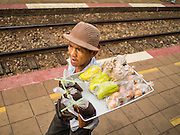 20 MARCH 2015 - KABIN BURI, PRACHINBURI, THAILAND:  A vendor sells fruit on a platform in the Prachinburi train station. He was selling snacks to passengers riding a 3rd class train to Kabin Buri. The State Railways of Thailand (SRT), established in 1890, operates 4,043 kilometers of meter gauge track that reaches most parts of Thailand. Much of the track and many of the trains are poorly maintained and trains frequently run late. Accidents and mishaps are also commonplace. Successive governments, including the current military government, have promised to upgrade rail services. The military government has signed contracts with China to upgrade rail lines and bring high speed rail to Thailand. Japan has also expressed an interest in working on the Thai train system. Third class train travel is very inexpensive. Many lines are free for Thai citizens and even lines that aren't free are only a few Baht. Many third class tickets are under the equivalent of a dollar. Third class cars are not air-conditioned.  PHOTO BY JACK KURTZ