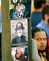 This picture story:  The fourth anniversary of the 9/11 disaster in New York brought family members back to Ground Zero to remember their loved ones.....This picture: A family member of a victim of the World Trade Center attack looks at an impromptu shrine on a telephone pole next to the site of the disaster on the fourth anniversary of the attack in New York September 11, 2005.