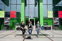 Female students sitting on swing seat outside the Stichting University of California the Netherlands building at Utrecht University in the Netherlands